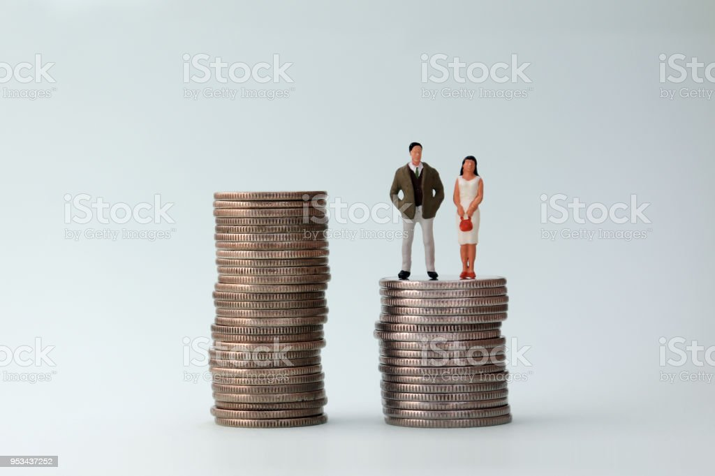 Two piles of coins with a miniature woman and miniature man. stock photo