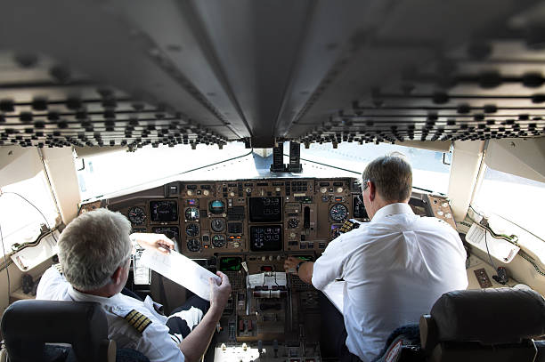 Two pilots in an airplane by the controls stock photo