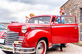 Two pin up girls standing by the vintage car.