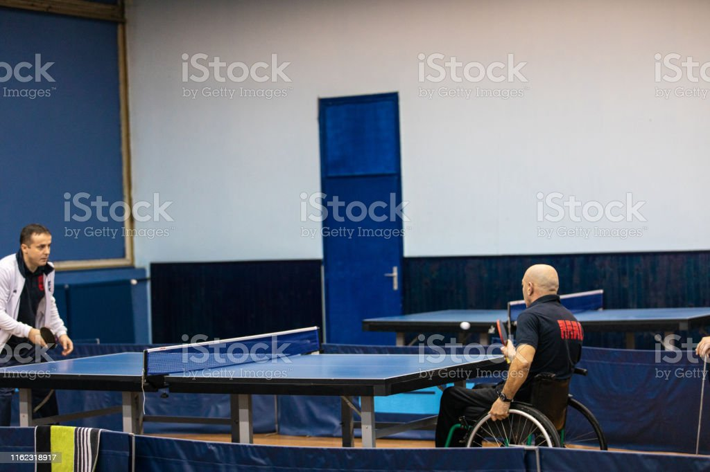 Two table tennis players playing ping pong indoor, one of them is in...