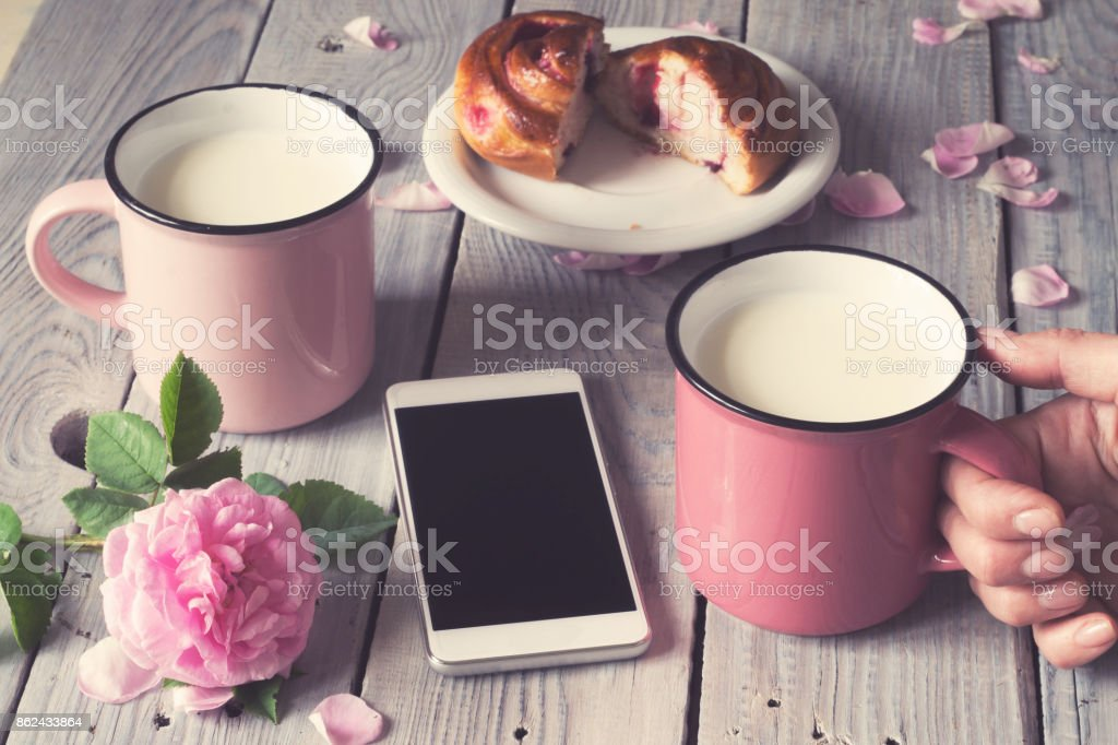 Two pink cups with milk on a white wooden table stock photo