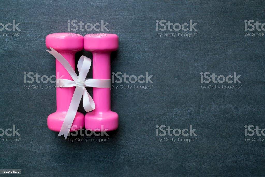 two pink dumbbell with white gift bow on a black table background, sport and healthy concept stock photo