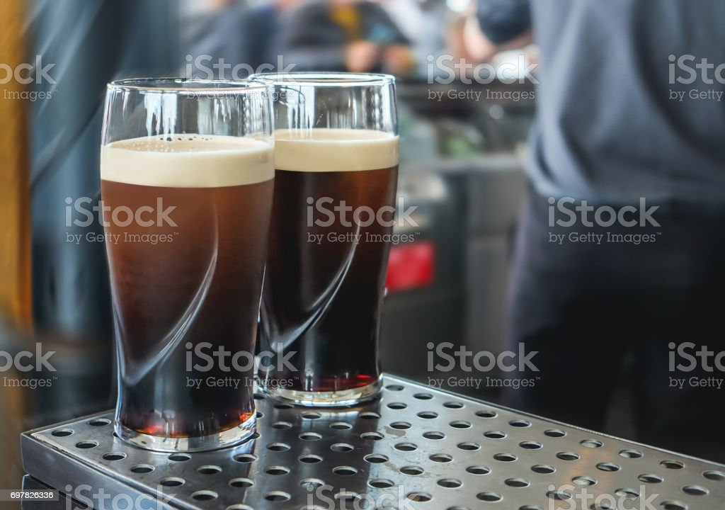 Two pint of  dark beer on the bar