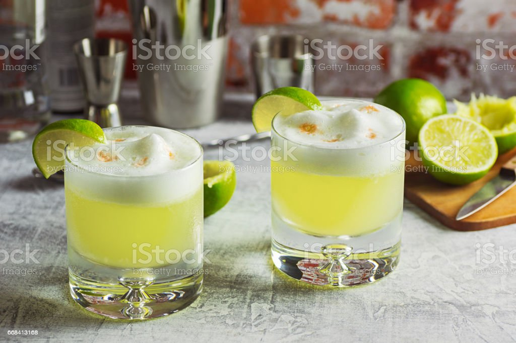 Two Pisco Sour Cocktails on the Bar with Ingredients Two rocks glasses filled with pisco sours and garnished with lime wedges on a bar top. This cocktail is made from Peruvian pisco liquor, lime juice, simple syrup, and egg white shaken together and topped with a couple dashes of bitters. The tools and ingredients used to make the drinks are in the background. Alcohol - Drink Stock Photo