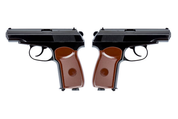 Two pistols symmetrically directed down the trunks stock photo