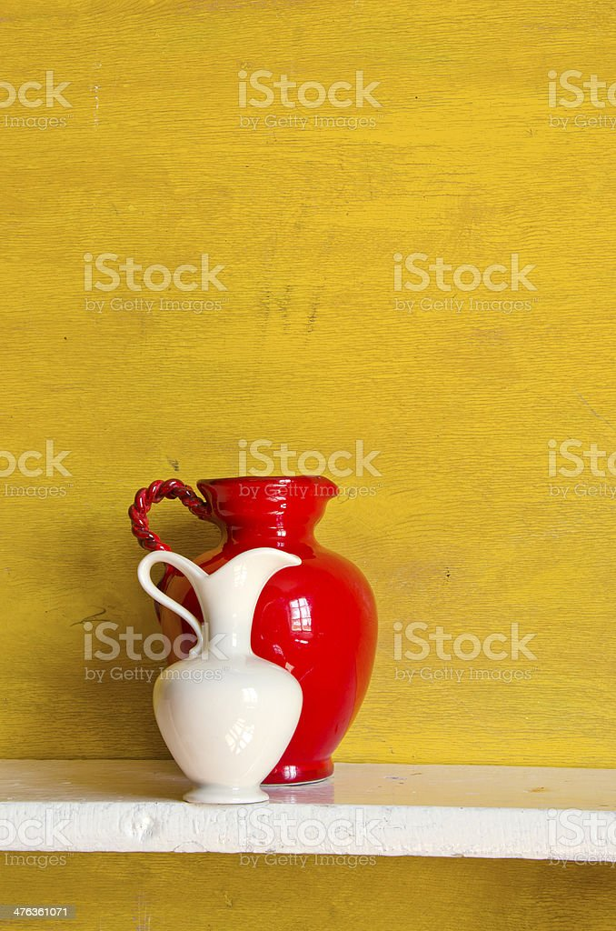 two pitchers on yellow background royalty-free stock photo