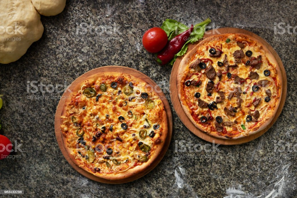 deux pizzas sont table en pierre sur la vue de dessus de cuisine - Photo de Aliment libre de droits