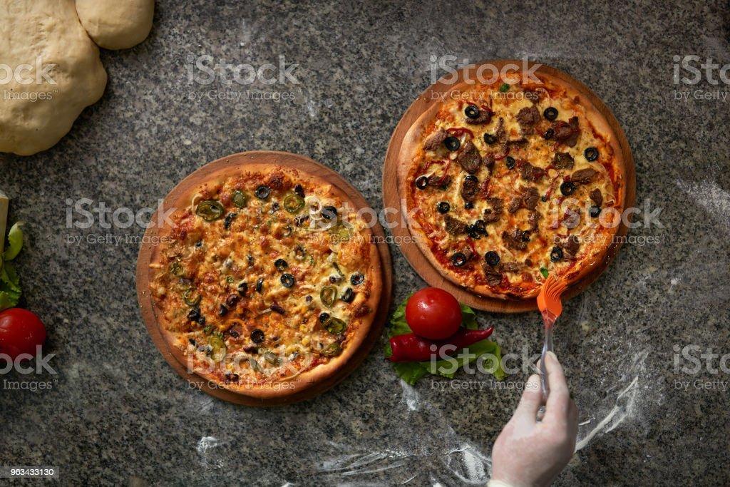 deux pizzas sont table en pierre sur la vue de dessus de cuisine. - Photo de Aliment libre de droits