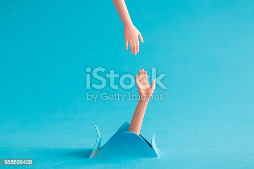 istock Two plastic hands on pastel blue background support abstract concept. 958696438