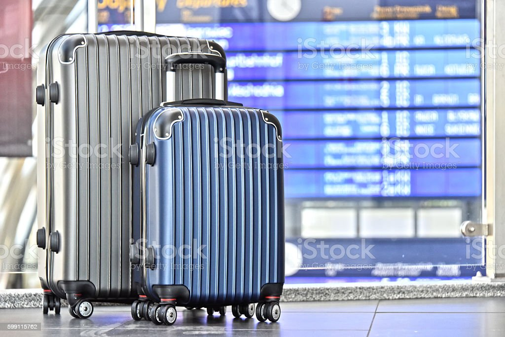 Two plastic travel suitcases in the airport hall stock photo
