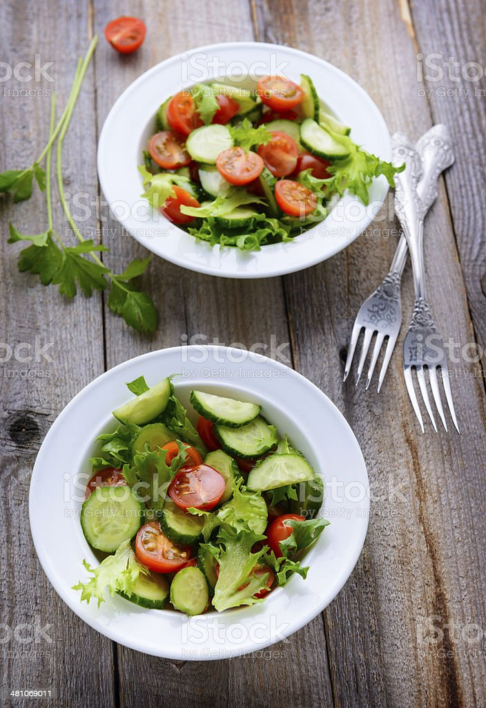 Two plates with fresh vegetable salad. Top view royalty-free stock photo