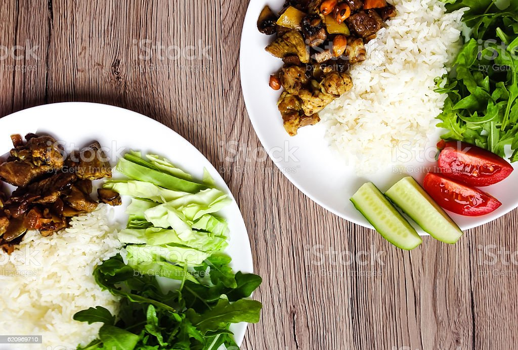 Two plates with healthy lunch. Rice, meat, vegetables. FLat lay stock photo
