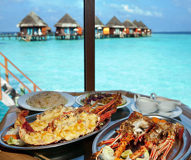 Two plates with lobster on table at window