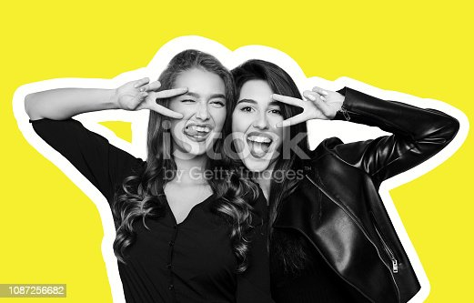 istock Two playful girls gesturing v-sign near eyes on yellow 1087256682