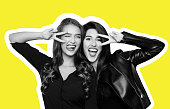 Magazine style collage of two foolish playful girls gesturing v-sign near winking eye, getting crazy at camera on yellow background