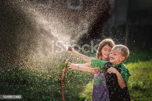 Happy little boy and girl playing with garden hose in the backyard.