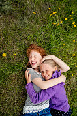 Two playful little girls lying on the grass in springtime.