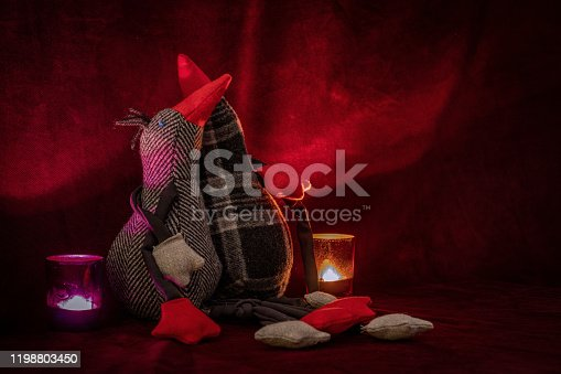 Romantic shot of two plush birds hugging each other on red velvet with two candlelights