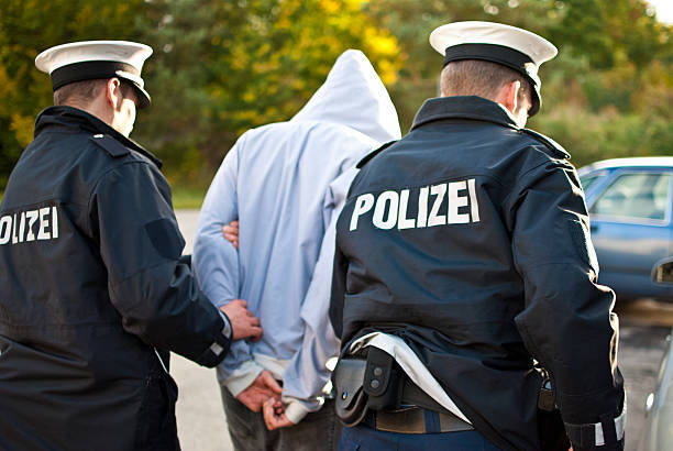 two police officers are frogmarching a suspect - german culture stock pictures, royalty-free photos & images