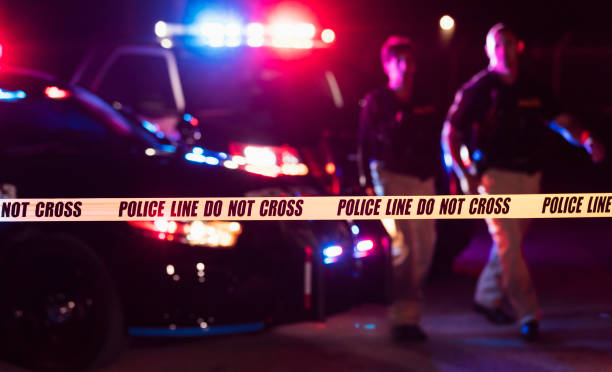 Two police officers behind crime scene tape stock photo