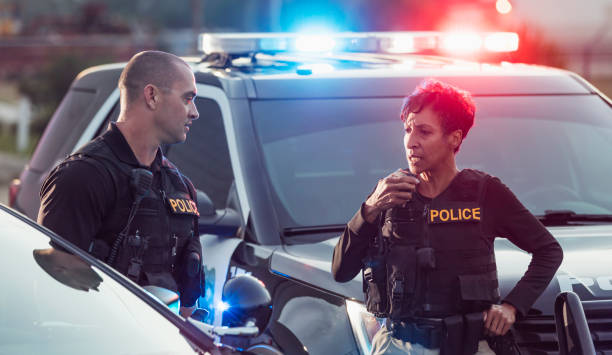 Two police officers by their patrol cars, on radio stock photo