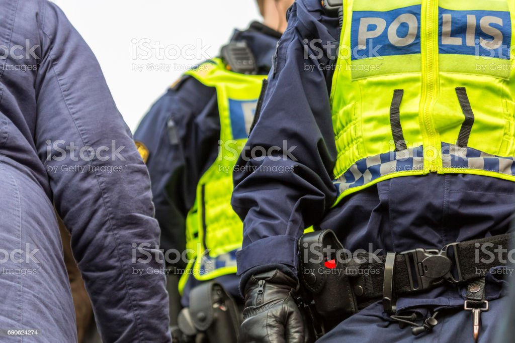 Two police officers in a crowd, close up of upper body with vest and equipment belt. stock photo