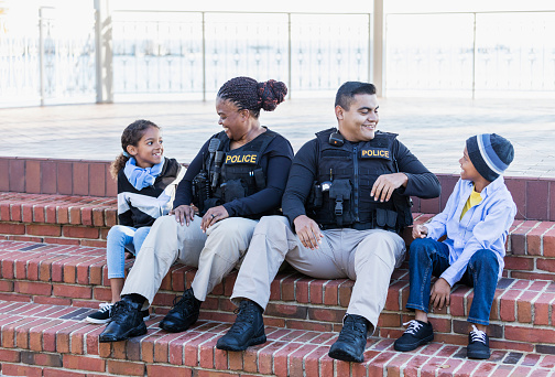 Community policing - two police officers hanging out with two young children, sitting side by side on steps outside a building. The officers are an African-American woman in her 40s and an Hispanic man in his 20s. The children are brother and sister, 8 and 7 years old, mixed race African-American and Caucasian.