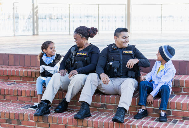 Two police officers in community, sitting with children stock photo