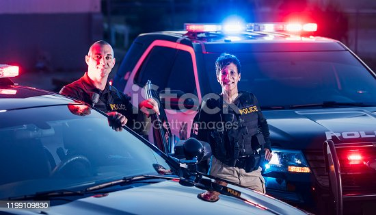 Two multi-ethnic police officers standing by the patrol cars, wearing bulletproof vests and duty belts. The policewoman is a mature African-American woman in her 40s. Her partner is a mid adult man in his 30s.