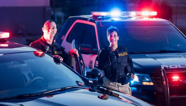 Zwei Polizisten stehen an ihren Streifenwagen – Foto