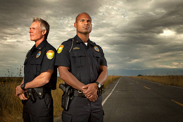 Two police officers standing on quiet road Police Officers. This stock image has a horizontal composition. Arm Badge Create by me, Gold Chest Emblem Custom Ordered Generic civil servant stock pictures, royalty-free photos & images