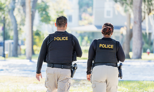 Community policing - rear view of two multi-ethnic police officers patrolling a local neighborhood on foot. They are walking side by side. The African-American policewoman is in her 40s. She and her partner, a young Hispanic man in his 20s.