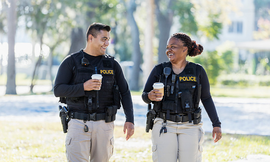 Community policing - two multi-ethnic police officers patrolling a local neighborhood on foot. They are walking side by side, conversing, drinking coffee. The African-American policewoman is in her 40s. She and her partner, a young Hispanic man in his 20s.