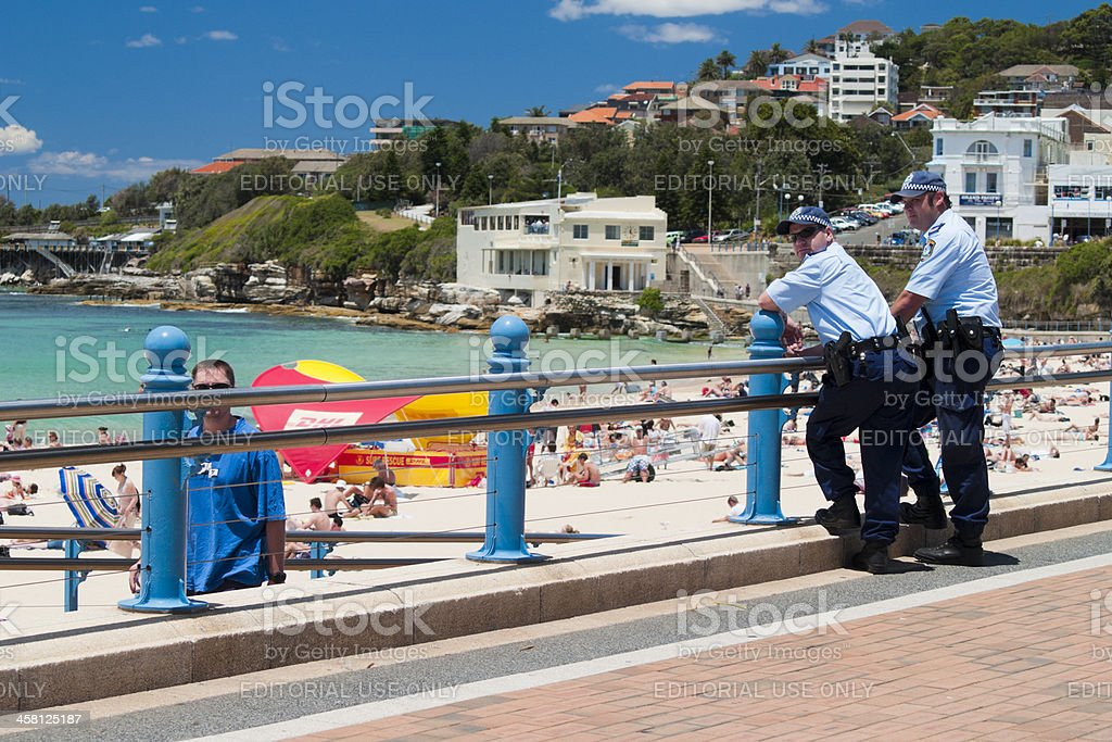 Two police officers watch the beach at Coogee, Sydney stock photo