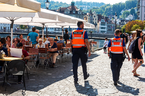 Lucerne, Switzerland - August 22, 2018: Two policemen providing security in front of restaurants of the Reuss River in Lucerne, Switzerland.