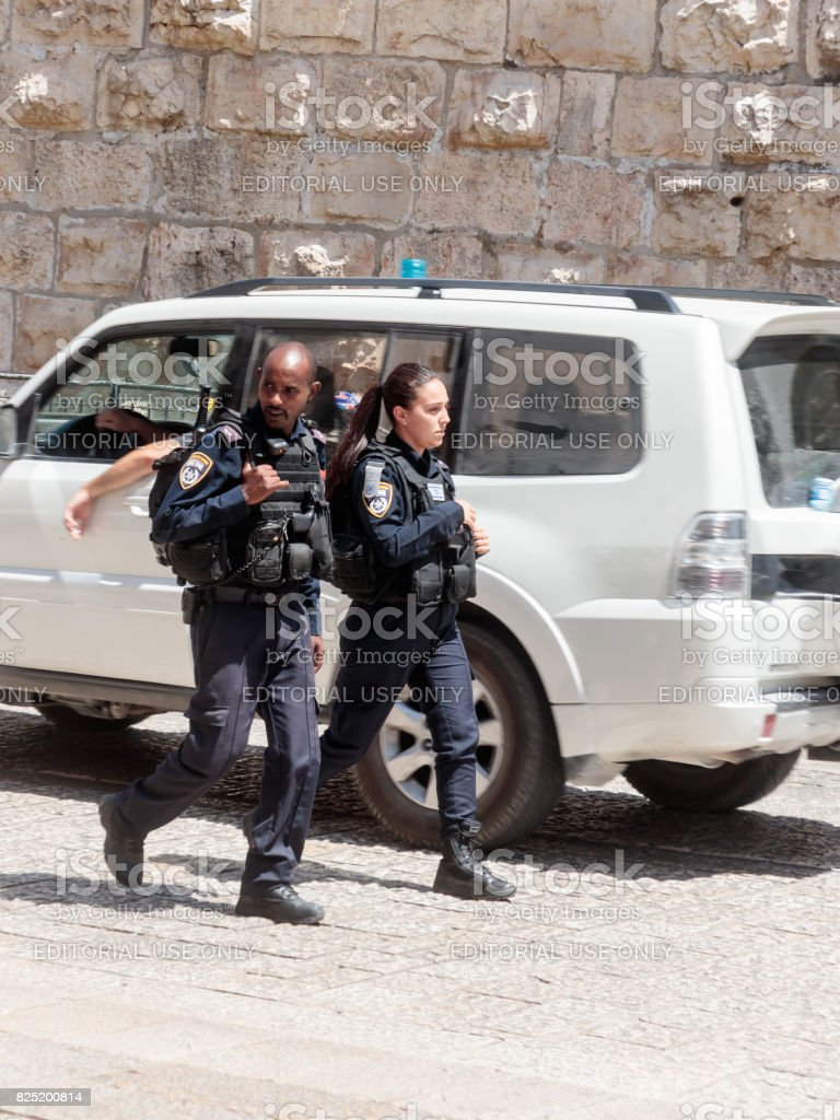 Two policemen patrol the streets in the old city of Jerusalem, Israel. stock photo