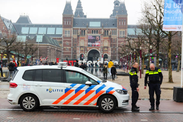 two policemen with a patrol car,With views of Amsterdam sign and Rijksmuseum Amsterdam,Holland Netherlands, March 2018, two policemen with a patrol car,With views of Amsterdam sign and Rijksmuseum museumplein stock pictures, royalty-free photos & images