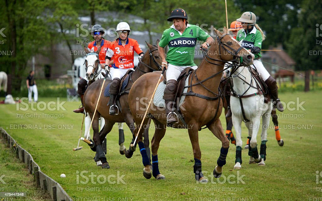 Two opposing polo teams challenging for the ball at the Jason Dixon...