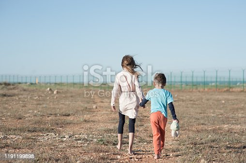 two poor children family brother and sister refugee illegal immigrant walking barefooted through hot desert towards state border with barbed fence wire