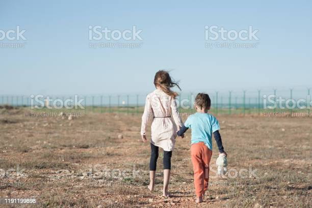Photo of two poor children family brother with toy and thin sister refugee illegal immigrant walking barefooted through hot desert towards state border with barbed fence wire