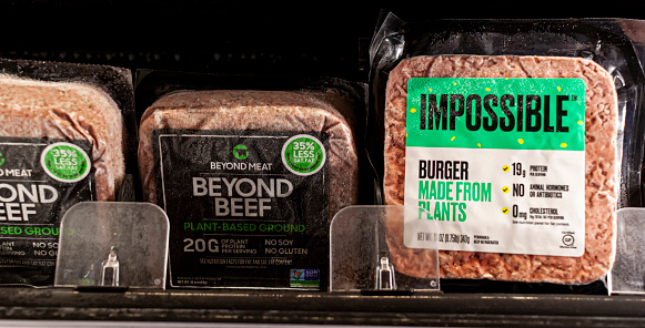 Germantown, MD, USA 01-15-2021: Two popular vegan meat alternative brands Impossible and Beyond beef are sold side by side on a grocery shelf. These are plant based cholesterol free products.