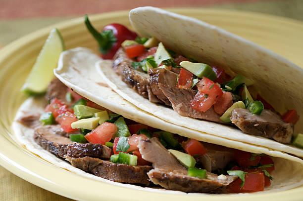 zwei weiche tacos mit schweinefleisch, tortillas mit salsa und limette - kräuterfaltenbrot stock-fotos und bilder