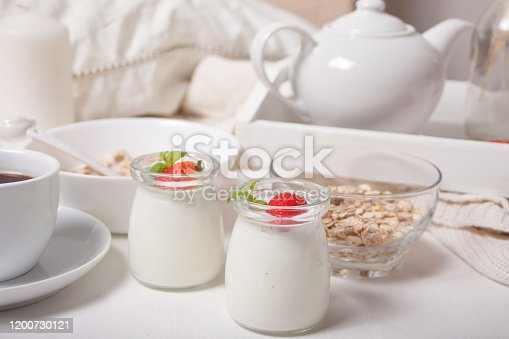 Two portions natural homemade yogurt in a glass jar with fresh strawberry and muesli nearby.