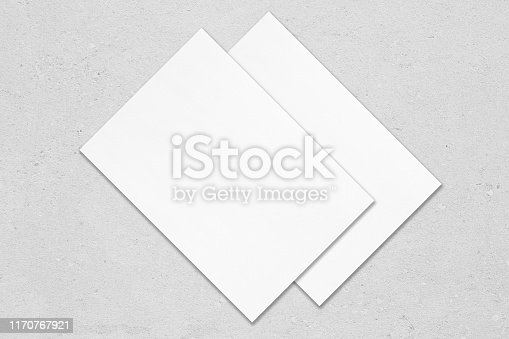 1171907064 istock photo Two poster mockups lying diagonally on top of each other on grey concrete background 1170767921