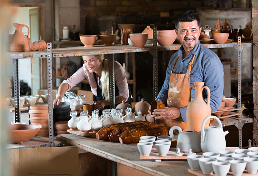 two potters working with ceramics in atelier