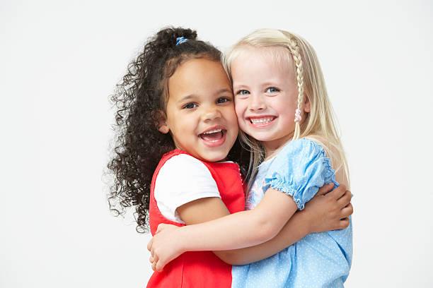 Zwei Mädchen umarmen vor der Schule, Andere – Foto