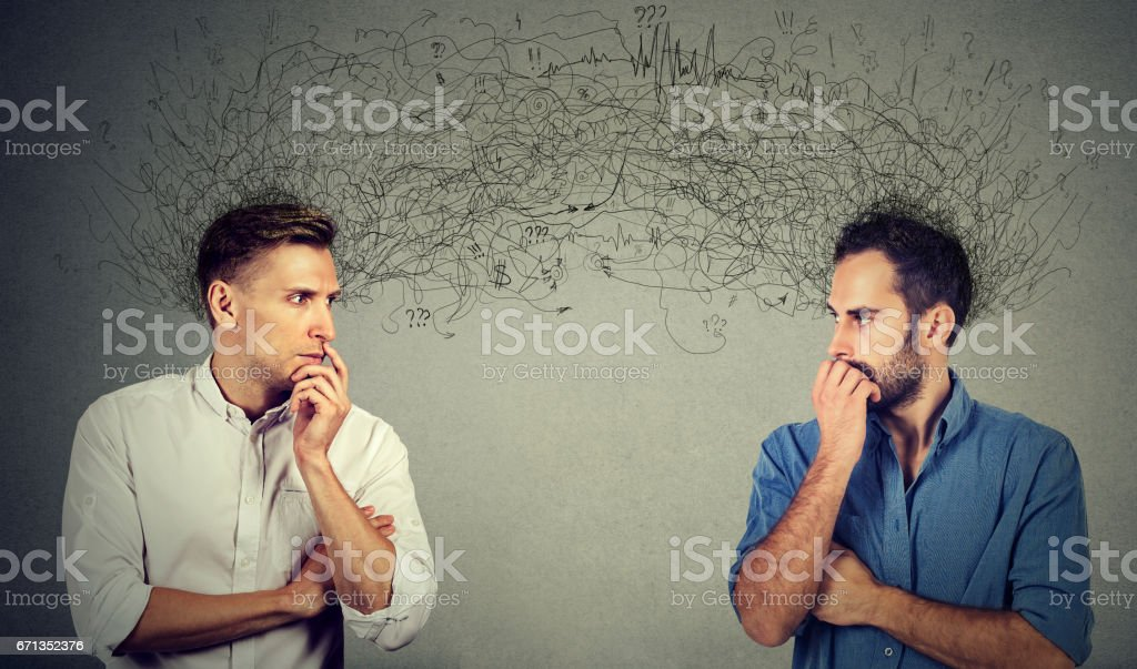 two preoccupied businessmen looking at each other exchanging with thoughts stock photo