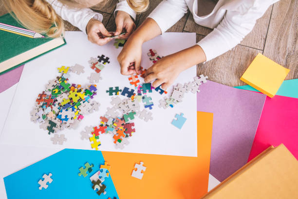 Two preschool age child put the puzzle together on the floor, hands close up stock photo