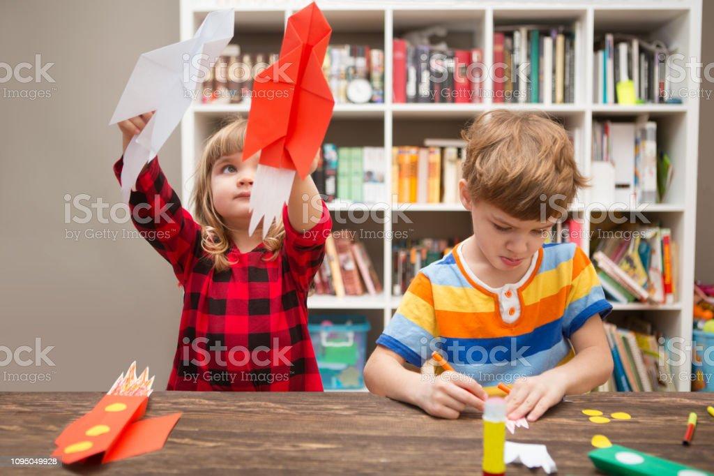 Zwei Kinder im Vorschulalter in Kreativität in der Heimat. Glückliche Kinder macht Raketen aus Papier und spielen. Die Kreativität der Kinder. Kreative Kinder spielen mit Handwerk. - Lizenzfrei Anfang Stock-Foto