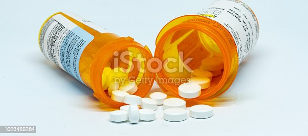 Two perscription bottles with pain pills spilling out of them with a white background.